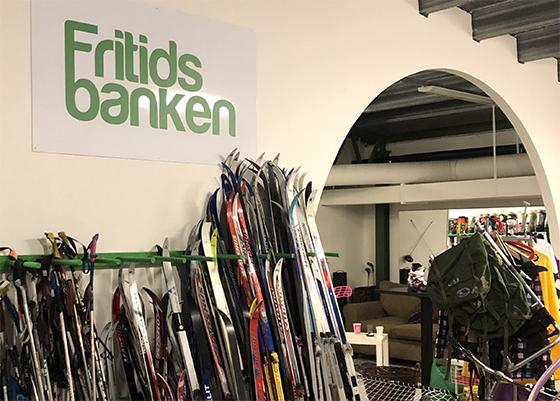 Vägg med Fritidsbankens logo och skidor som står lutade mot väggen.