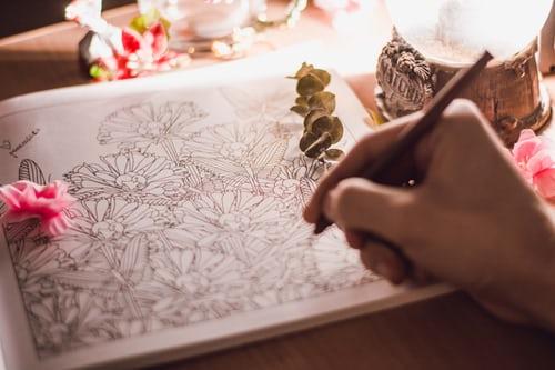 En person färglägger en mandala