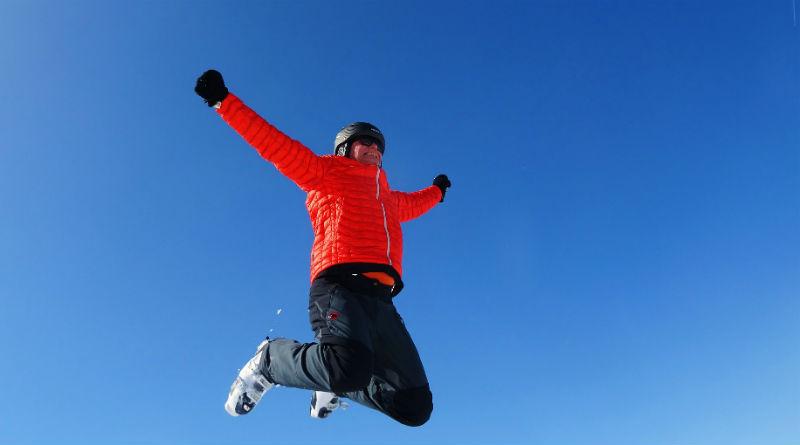 En man i röd skidjacka och hjälm hoppar med armarna utsträcka, och mot bakgrund av en klarblå himmel.