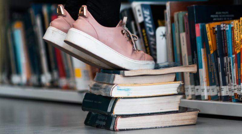 En person har byggt en pall av böcker på biblioteket för att nå högre upp på hyllorna