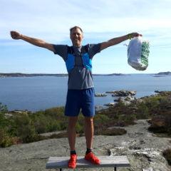 Plogga-grundaren Erik Ahlström står i träningkläder med en full soppåse i skärgården.