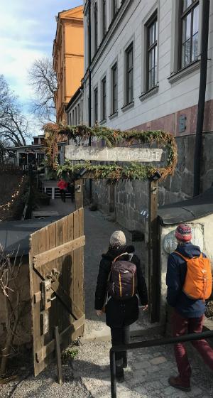 Besökare på väg in till den veganska restaurangen Hermans. En portal med texten Hermans trädgårdscafé välkomnar gästerna.