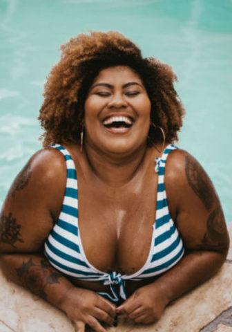 En skrattande kvinna i bikini. Foto: Unsplash