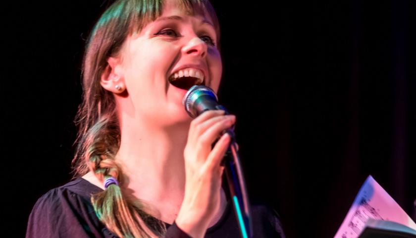 En person som sjunger i kör, håller i en mikrofon och noter